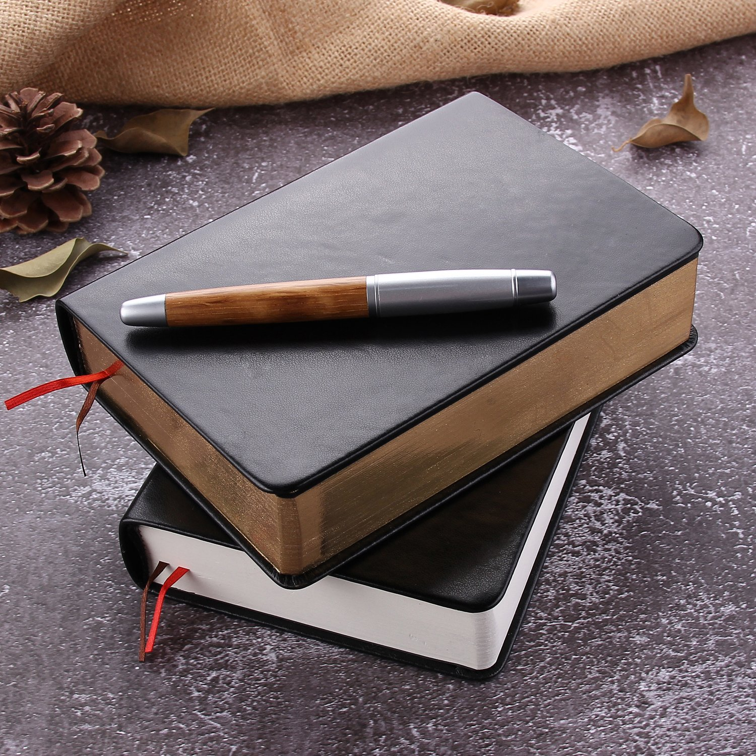 Two vintage style notebooks stacked with a wood grained pen on top.