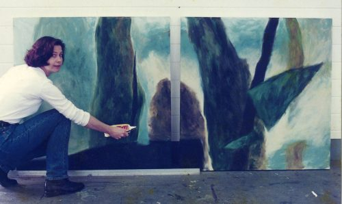 Artwork - Image of the artist beside a painting of a landscape